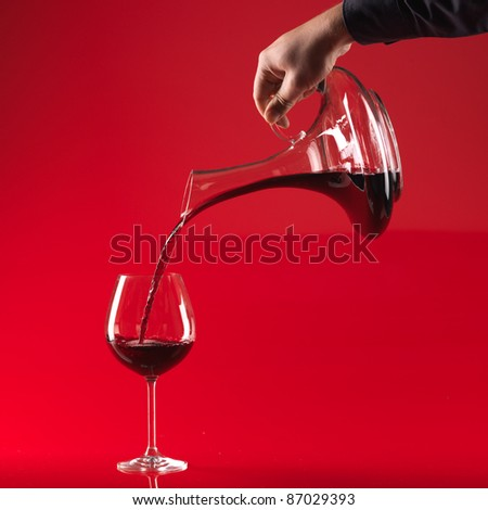 man's hand pouring red wine from decanter in glass, on red background