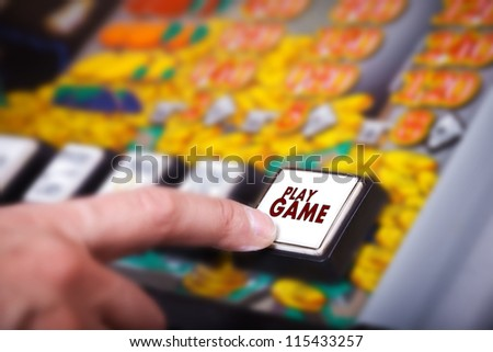 Man's hand pressing play button on a slot machine