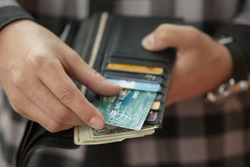 Man's hand pulls out a credit card from a black purse