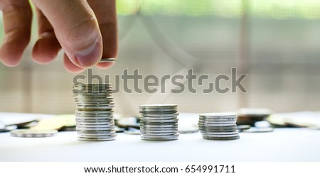 Man's hand put money coins to stack of coins. Money, Financial, Business Growth concept. #654991711