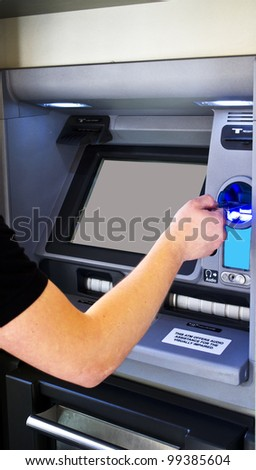man's hand puts bank card into ATM