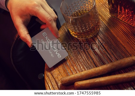 Man's hand puts exclusive membership card on the table. Gentleman's hand puts exclusive membership card on the wooden table with whisky in carafe and glass with cigars. Stock photo ©