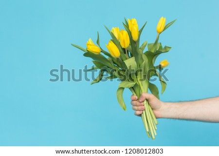 Man's hand reaching out a bunch of yellow tulips on blue background with copy space #1208012803