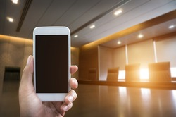 Man's hand shows mobile smartphone in vertical position and blurred meetingroom background - business mockup template