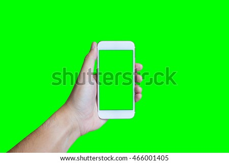 Man's hand shows mobile smartphone with green screen in vertical position isolated on green background - mockup template and clipping path #466001405