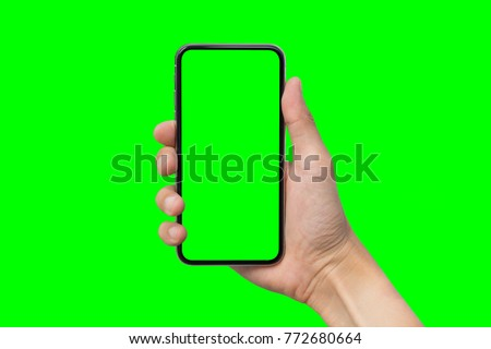 Man's hand shows mobile smartphone with green screen in vertical position isolated on green background. Mock up mobile #772680664