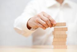 Man's hand stacking wooden blocks. Business development concept.
