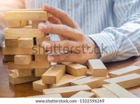 Man's hand stacking wooden blocks. Business development concept #1102596269