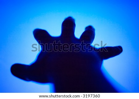 Man's hand stretching to TV blue screen. Low DOF and high contrast.