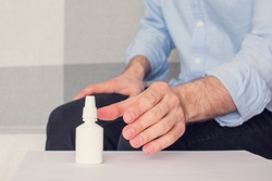 Man's hand takes a nose spray for the nose, close-up