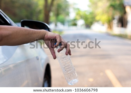 man's hand throwing plastic bottle out of car window, close up