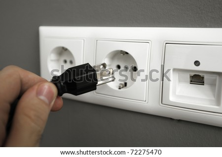Man's hand trying to plug an american type of plug to an european outlet. This photograph is a great methaphor for for saving electrical energy worldwide