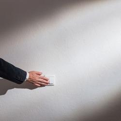 Man's hand turns on the light