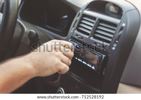 man's hand twists the volume in a retro toning car.