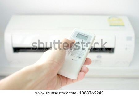 Man's hand using remote control open The air conditioner is cooled to 25 degrees Celsius in his bedroom. Health concepts and energy savings
