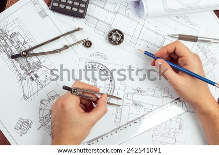 Man\'s hand with a compass. Mechanical engineer at work. Technical drawings. Pencil, compass, calculator and hand man. Paper with technical drawings and diagrams.