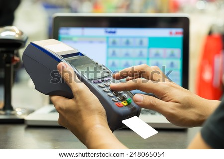 man\'s hand with credit card swipe through terminal for sale in store