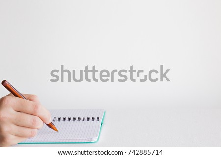 Man's hand with pen writing something in the notebook on the table. Education concept. Empty place for a important ideas, plans, memories, messages, to do lists or other text. #742885714