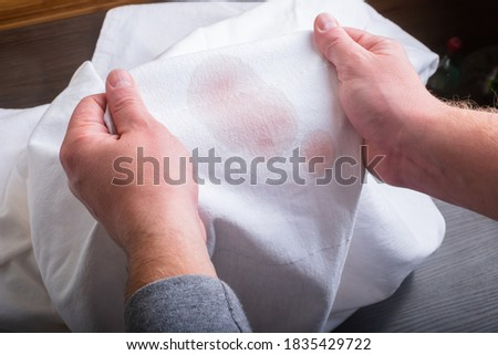 Man's handing hold clothes with a stain from wine.top view Stock fotó ©
