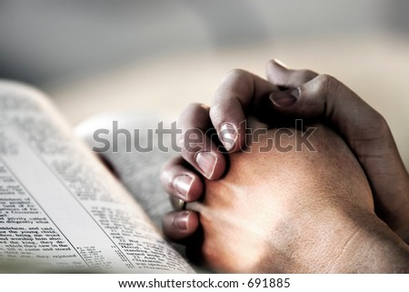 Man\'s hands clasped in prayer over a Holy Bible - represents faith and spirituality in everyday life.