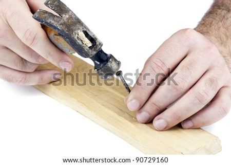 Man's hands hitting a nail on the head with old and used wood hammer on white background.