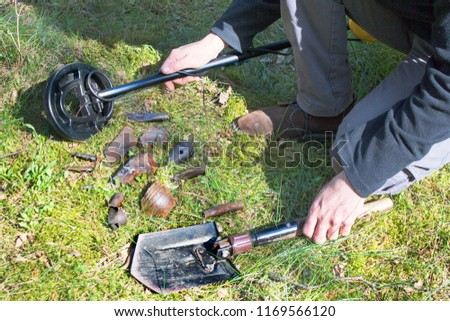 Man's hands hold a metal detector and a shovel. The found militaria lie on moss and grass.