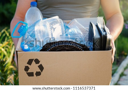 Man's hands holding a carton with plastic garbage for recycling. Recycle concept