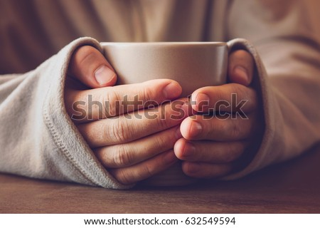 Man's hands holding a mug and warming with hot tea in the evening.