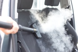 Man's hands holding a steam cleaner cleaning stinky car interior, lots of vapor, clean without chemicals concept