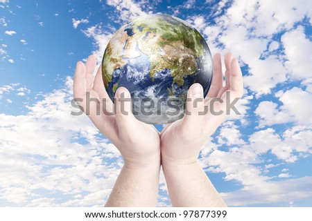 Man's hands holding on globe on cloudy blue sky. Concept for environmental protection from global warming. Data source: Nasa - stock photo