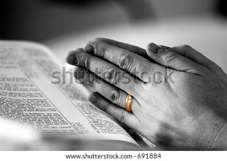 Man's hands in prayer over a Holy Bible, with a gold wedding band highlighted - represents faith and spirituality in life and marriage. - stock photo