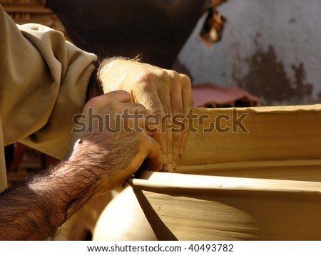man's hands of the handicraftsman of the potter doing a clay pot