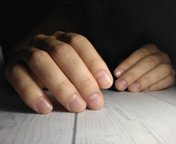 Man's hands on manicure. Processing of male fingers. Long untrimmed nails with untreated cuticle on a dark background.