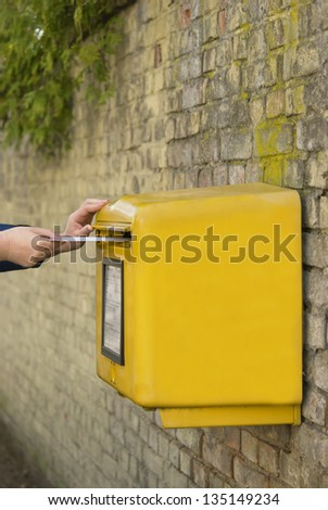 Man\'s hands posting a letter in a yellow post box, stone wall background