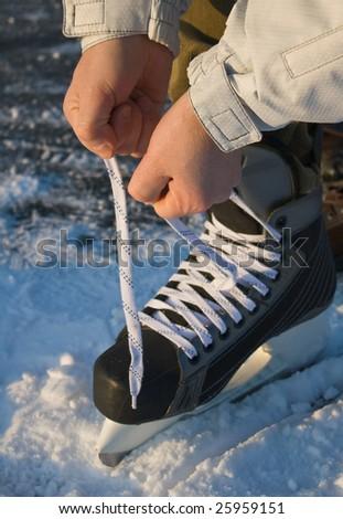 man's hands tying ice skate