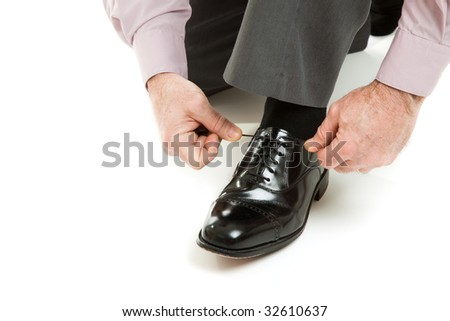 Man's hands tying shoelace of his new oxford shoes.  Isolated on white.