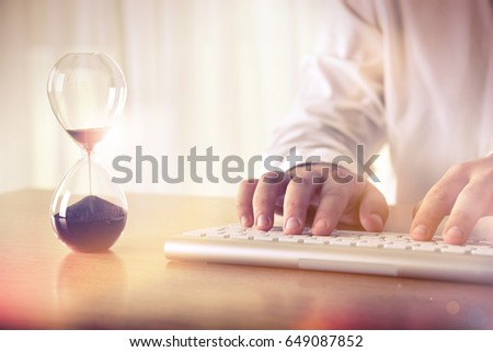 Man's hands typing on computer keyboard next to a hourglass. Concept of time management, business schedule and deadline, for background, website banner, promotional materials, advertising. #649087852