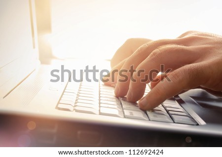 Man's hands typing on laptop keyboard #112692424