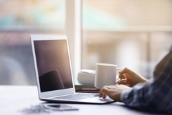 Man's hands using laptop and holding cup of tea at the table
