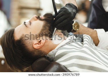 Man\'s hands wearing black gloves and watch making a beard form with razor for man with dark hair and beard at barber shop, portrait, close up.