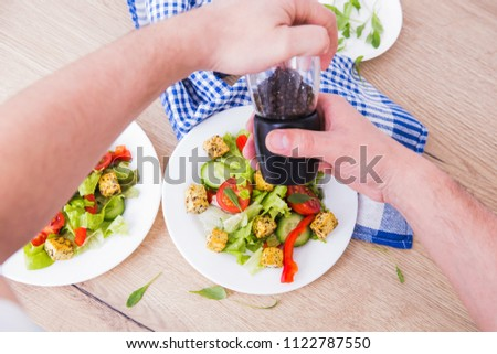 Man's hands with pepper-pot. Two portions of soy cheese vegetarian salad with vegetables.