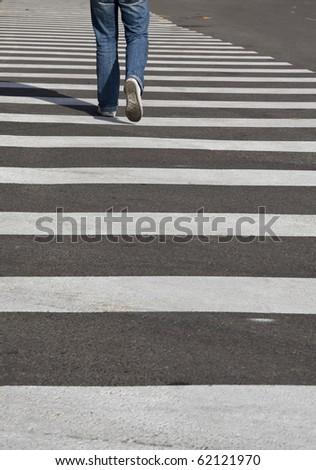 man's legs crossing the street