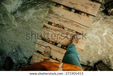 Man's legs on an old wooden bridge through the river #371905453