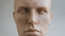 Man's plastic head dummy on a light background close-up
