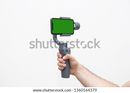 Man's right hand holding a gimbal stabilizer with mobile phone with green screen in  horizontal mode in a white background