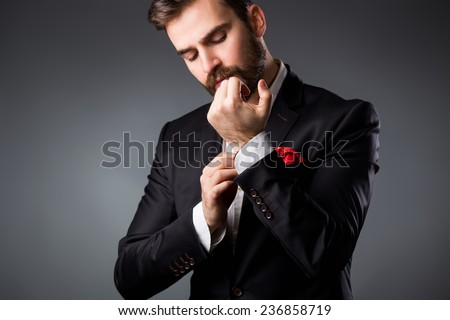 Man's style. Elegant young man getting ready. Dressing suit, shirt and cuffs ストックフォト ©