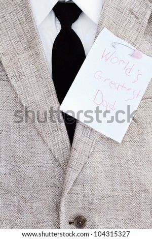 Man's suit jacket, tie and shirt with World's Greatest Dad note pinned over his heart.