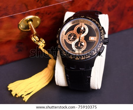 Man's wristwatch and locked jewelry box and key in the background