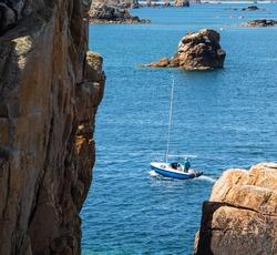 Man sailing boat between rocks at Pink Granite Coast, Plougrescant, Cotes-d'Armor, France.