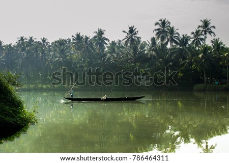 man sailing boat in kerala backwaters